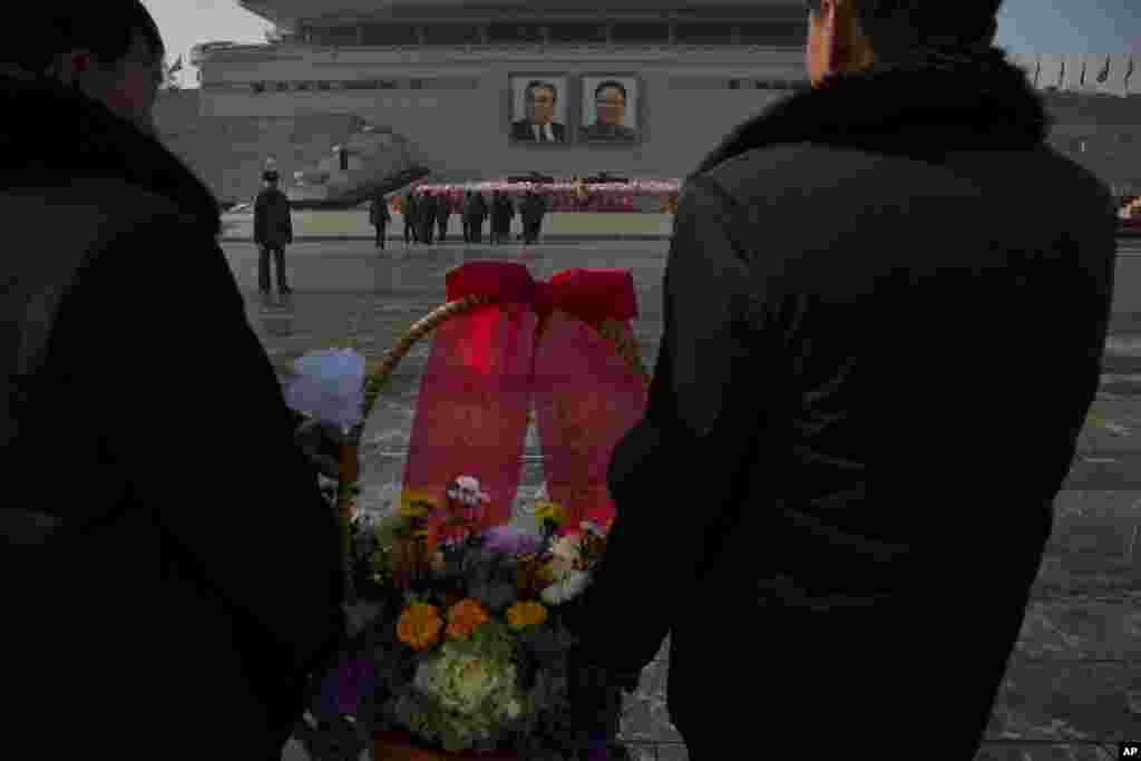 North Koreans lay flowers beneath portraits of the late leaders Kim Jong Il and Kim Il Sung in Pyongyang, Dec. 17, 2013.
