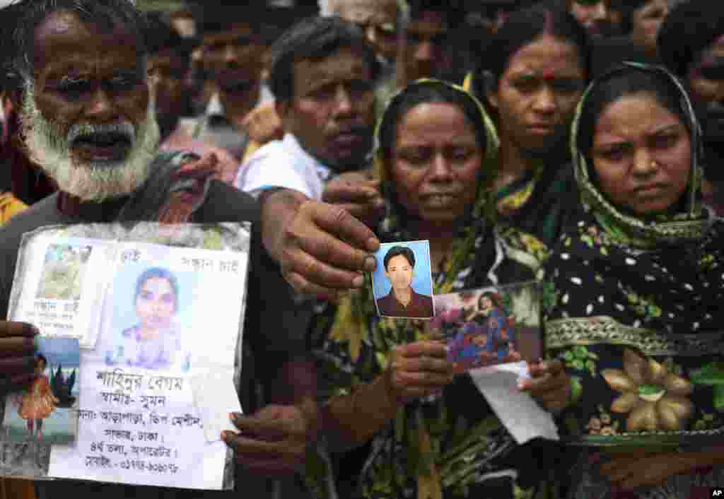 A man holds out a picture of his missing relative on Monday April 29, 2013 in Savar, near Dhaka, Bangladesh.