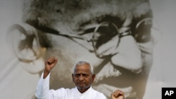 Veteran Indian social activist Anna Hazare raises his fist in front of a portrait of Mahatma Gandhi at Ramlila grounds in New Delhi, Aug. 19, 2011.