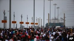 Thousands of spectators watch as the Neopanamax cargo ship, Cosco Shipping Panama, prepares to cross the new new Agua Clara locks, part of the Panama Canal expansion project, near the port city of Colon, Panama, June 26, 2016.