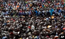 """Supporters of opposition leader Raila Odinga, one wearing a mask, attend a mock """"swearing-in"""" ceremony at Uhuru Park in downtown Nairobi, Kenya, Jan. 30, 2018."""