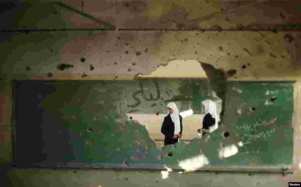 Palestinian students look inside a classroom that witnesses said was shelled by Israel during its offensive, on the first day of the new school year east of Gaza City.