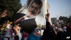An Egyptian woman holds a portrait of ousted Egyptian President Mohamed Morsi during a protest in Nasr City in Cairo, Nov. 1, 2013.