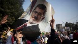 ແມ່ຍິງຄົນນຶ່ງກຳລັງຍົກ ຮູບພາບ ປະທານາທິບໍດີ Morsi ໃນລະຫວ່າງການປະທ້ວງ ໃນກຸງໄຄໂຣ ວັນທີ 1 ພະຈິກ 2013.