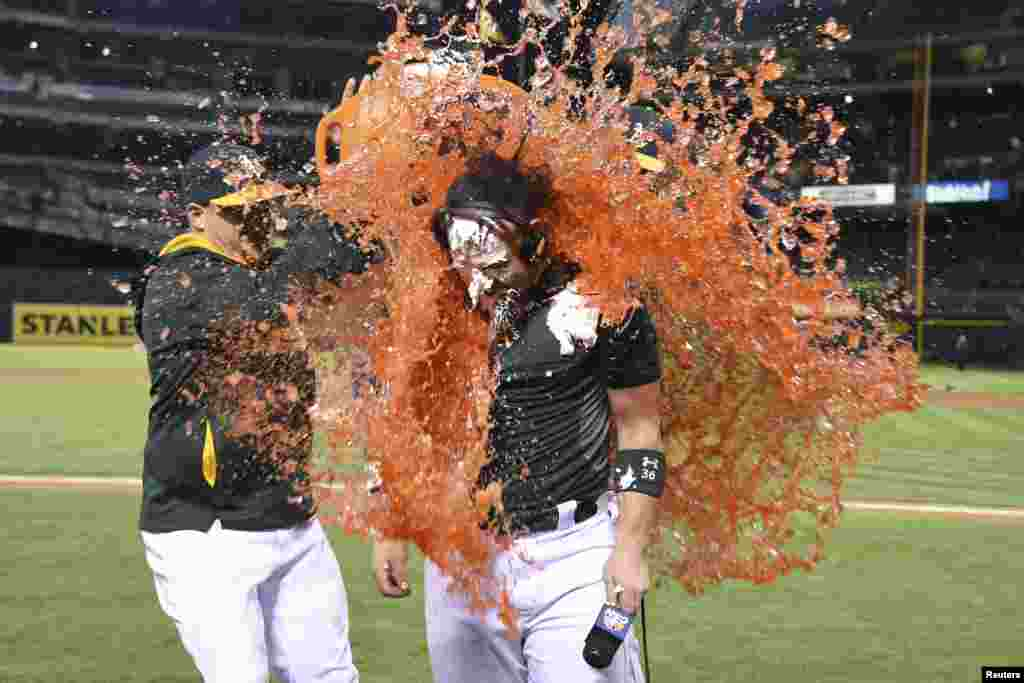 Oakland Athletics first baseman Stephen Vogt (21, left) dumps Gatorade on catcher Derek Norris (36, right) after Norris hit the game-winning RBI-single during the 10th inning against the Tampa Bay Rays at O.co Coliseum, Oakland, California, USA, Aug. 4, 2014. (Credit: Kyle Terada-USA TODAY Sports)