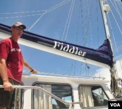 """James Hilliard, anggota termuda dari generasi Hilliard yang berpartisipasi dalam """"Sail Sabang Regatta"""" berpose dengan kapal layar Fiddler."""