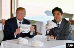 """在东京附近的高尔夫球场俱乐部共进午餐时,唐纳德·川普和安倍晋三在白色球帽上签名,帽子上印着""""唐纳德和晋三使同盟更伟大""""(2017年11月5日)"""