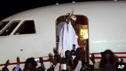 L'ex-président gambien Yahya Jammeh salue ses partisans avant d'entrer à bord de l'avion en destination de la Guinée équatoriale, à l'aéroport de Banjul, Gambie, 21 janvier.
