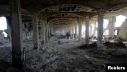 A Palestinian worker walks inside al-Awdah food factory, which witnesses said was shelled and torched by the Israeli army during the offensive, in Deirl al-Balah, central Gaza Strip, Aug. 14, 2014.