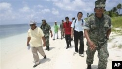 Armed Forces of the Philippines Western Command commander Lt. Gen. Juancho Sabban, right, Kalayaan municipality Mayor Eugenio Bito-onon, 2nd right, and Philippine Congressman Walden Bello, 3rd right, walk along the shores of Pagasa Island, part of the dis