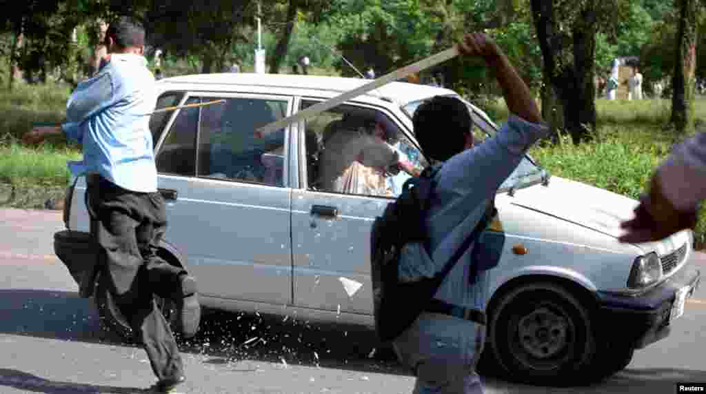 Protesters use sticks to smash the windscreen and windows of a car during an anti-America protest march in Islamabad September 20, 2012.