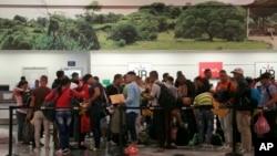 Migrantes cubanos hacen sus trámites de salida en el aeropuerto Daniel Odúber de Liberia, Costa Rica. Un segundo grupo de migrantes salió el jueves por la noche hacia El Salvador.