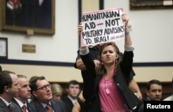 A protester holds a sign as U.S. Defense Secretary Ash Carter and U.S. Joint Chiefs Chairman General Martin Dempsey (unseen) testify before a House Armed Services Committee hearing on Capitol Hill in Washington, June 17, 2015.
