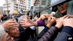 Seorang perempuan Korea Utara yang tidak diketahui identitasnya mengulurkan tangannya untuk menggenggam tangan keluarganya di Korea Selatan ketika berpisah setelah reuni keluarga di Korea Utara, 22 Oktober 2015.
