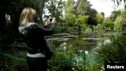 A woman takes pictures from the bridge at the nympheas pond garden as she visits the reopened Claude Monet house and foundation after restrictions to prevent the spread of COVID-19 were eased, in Giverny, France, June 9, 2020. (REUTERS/Benoit Tessier)