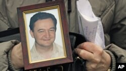 A November 2009 photo shows a portrait of Russian lawyer Sergei Magnitsky who died in jail, held by his mother Nataliya Magnitskaya in Moscow.