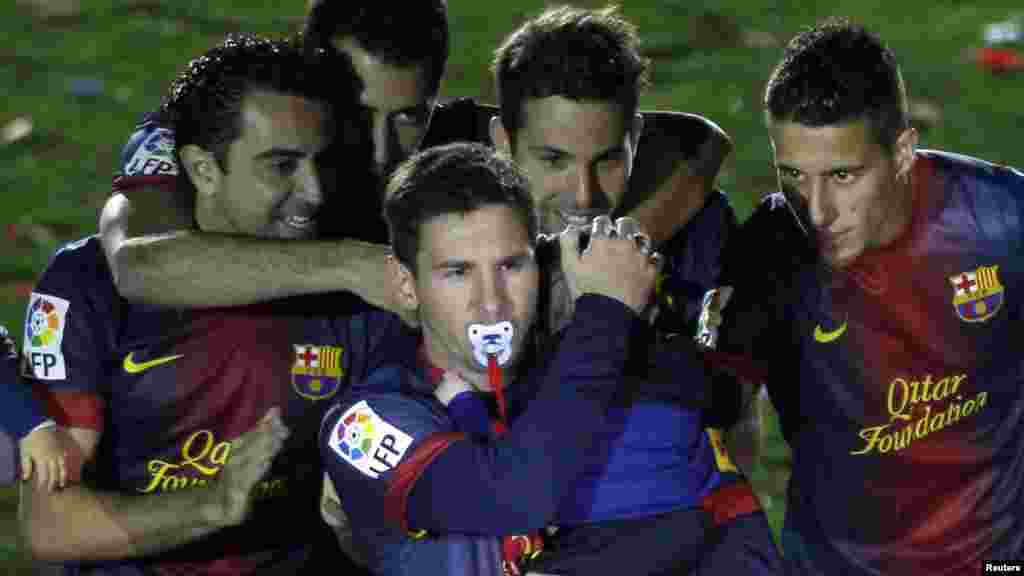 Barcelona's Lionel Messi, with a dummy in his mouth, carries his son Thiago near his team mates during the Spanish league first division trophy celebrations in Barcelona May 19, 2013.