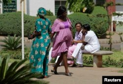 FILE - A pregnant woman walks past health care workers outside the hospital in Abuja, Nigeria, March 5, 2013.