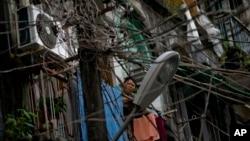 Seorang perempuan berdiri di balkon rumahnya yang berhimpitan dengan kabel-kabel listrik dan telepon yang bergantungan tidak teratur di wilayah Yangon, Burma (25/9).