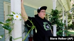 Gavin Grimm leans on a post on his front porch during an interview at his home in Gloucester, Va. Grimm is a transgender student whose demand to use the boys' restrooms has divided the community and prompted a lawsuit.