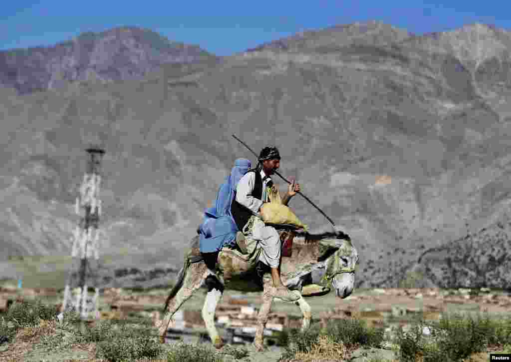 A family rides on a donkey as they travel along a road on the outskirts of Parwan province, Afghanistan.