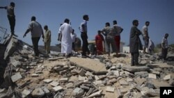 In this photo taken on a government-organized tour, Libyan men stand on top of the remains of a medical clinic that was destroyed during a NATO airstrike early Monday morning, in the town of Zlitan, roughly 160 km (99 miles) east of Tripoli, Libya, Monday