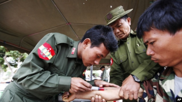 A soldier injects medicine into an earthquake survivor at a temple in Mine Lin village, Burma, March 27, 2011.