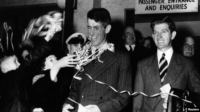 In this August 8, 1953 file photo, Sir Edmund Hillary, left, and his fellow New Zealander George Lowe, are welcomed home to New Zealand following their arrival by air at Auckland.