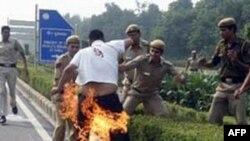 Cảnh sát Ấn Ðộ cố gắng dập tắt lửa trên người Sherab Tsedor, thanh niên Tây Tạng tự thiêu bên ngoài Ðại sứ quán Trung Quốc ở New Delhi, Ấn Ðộ