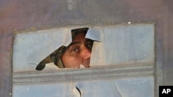 Припадник на специјалните полициски сили фрла поглед од оклопно возило во Куманово