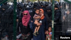 Migrants are sent back by Hungarian riot police at the border crossing with Serbia in Roszke, Hungary, September 16, 2015. Hungarian police fired tear gas and water cannon at protesting migrants demanding they be allowed to enter from Serbia on the second day of a border crackdown.