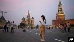FILE - A young woman checks her smartphone at Red Square in Moscow, Russia, July 2016. (AP Photo/Pavel Golovkin)