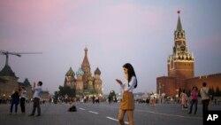 Seorang wanita muda memegang telepon genggamnya di Lapangan Merah dengan latar belakang Menara Spasskaya Kremlin (kanan) dan Katedral St. Basil (tengah) di latar belakang di Moskow, Rusia, Senin, 25 Juli 2016. (AP Photo / Pavel Golovkin)