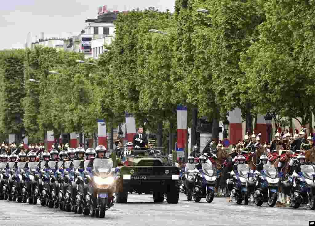 Newly-elected President Emmanuel Macron parades on a military car following his formal inauguration ceremony as French President in Paris.