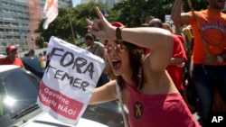 """ຜູ້ປະທ້ວງຄົນໜຶ່ງ ຖືປ້າຍ ທີ່ອ່ານວ່າ holds a sign that reads """"Temer ຈົ່ງອອກໄປ"""" ໃນລະຫວ່າງ ການປະທ້ວງຕໍ່ຕ້ານປະທານາທິບໍດີ ຂອງ ບຣາຊິລ ທ່ານ Michel Temer ຢູ່ທີ່ ຊາຍຫາດ Copacabana, ໃນ Rio de Janeiro, ບຣາຊີລ, ວັນອາທິດ ທີ 4 ກັນຍາ 2016."""