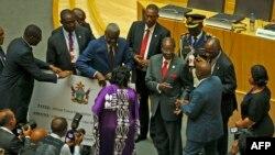 El presidente de Zimbabwe, Robert Mugabe (centro) donó $1 million de dólares a la Unión Africana, el lunes, 3 de julio de 2017.