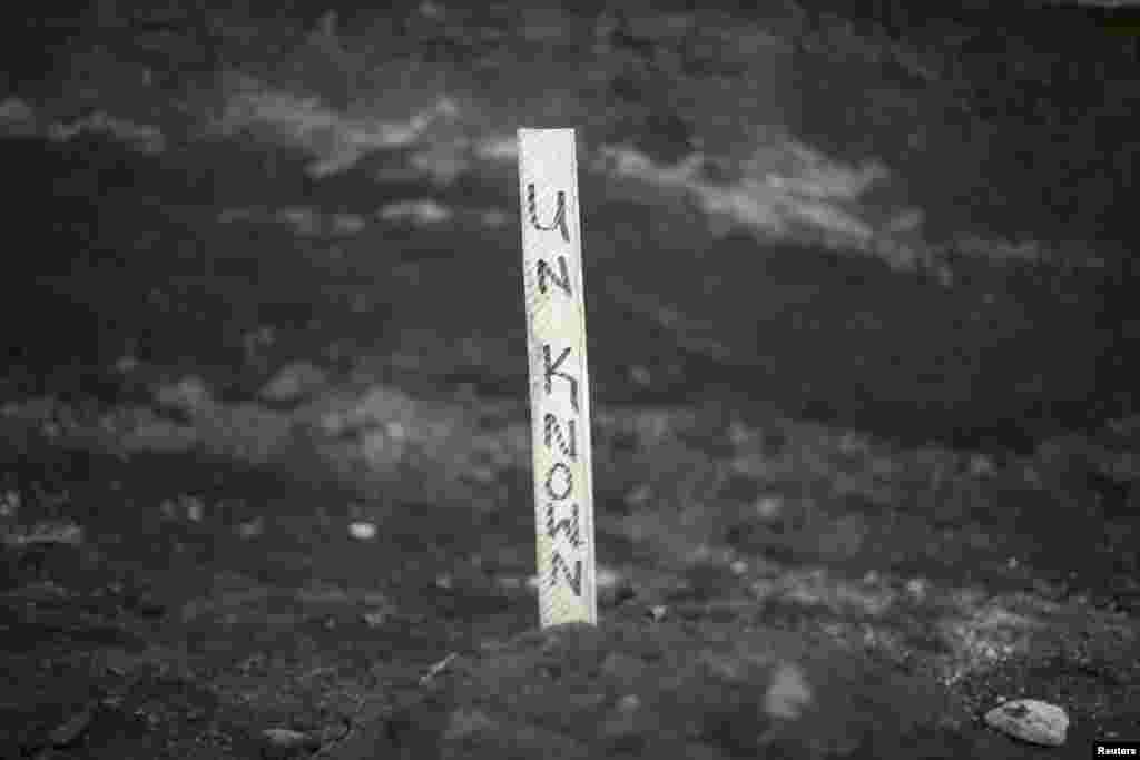 Un écriteau avec le nom d'une victime d'Ebola non identifiée enterrée dans un cimetière à Freetown, 17 décembre 2014. REUTERS / Baz Ratner