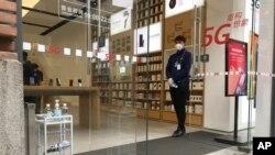 武漢周一解封,一家重新開門的商店的營業員在門口等候顧客。 (2020年3月30日)