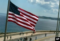 FILE - The U.S. flag waves outside the newly opened U.S. Embassy, overlooking Havana's seaside boulevard, the Malecon in Cuba, Aug. 14, 2015.