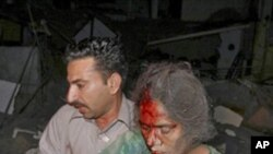 A Pakistan man helps an injured woman from the site of a deadly car bomb explosion in Karachi, Pakistan, 11 Nov. 2010.