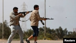 FILE - Fighters from Misrata fire weapons at Islamic State militants near the coastal city of Sirte, Libya, March 15, 2015.