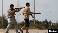 Des combattants de Misrata tirent des armes sur des militants du groupe Etat islamique près de Syrte le 15 mars 2015
