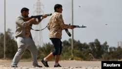 FILE - Fighters from Misrata fire weapons at Islamic State militants near Sirte, March 15, 2015. Militants loyal to Islamic State, the group that has seized much of Iraq and Syria, have established a larger presence in Libya.