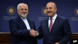 FILE - Foreign ministers Mohammad Javad Zarif of Iran, left, and Mevlut Cavusoglu meet in Ankara, Turkey, Aug. 12, 2016. Cavusoglu said he made a surprise visit to Tehran to enhance cooperation on Syria.