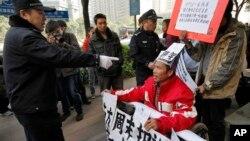 Cảnh sát nói với một người ngồi trên xe lăn, ủng hộ cho báo Nam Phương (Southern Weekly) về vấn đề kiểm duyệt, trước khi đưa ông đi nơi khác