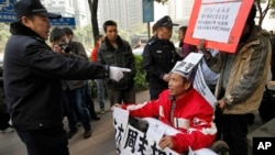 A policeman points to a supporter of Southern Weekly newspaper in a wheelchair before taking him away during a protest in Guangzhou, Guangdong province, China, Jan. 10, 2013.