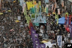 FILE - Protesters carry a large image of jailed Chinese Nobel Peace laureate Liu Xiaobo as they march during a pro-democracy protest in Hong Kong, July 1, 2017.