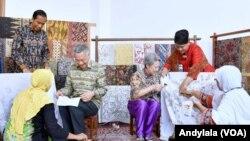 Perdana Menteri Singapura Lee Hsien Loong dan istri Ho Ching mencoba menuliskan pola batik di atas kain mori disaksikan Presiden Jokowi dan Ibu, 14 November 2016 (Foto: VOA/Andylala)