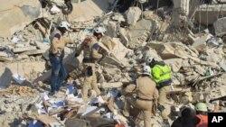 救援人员在叙利亚伊德利卜市据信被俄罗斯空袭摧毁的建筑废墟里寻找幸存者 (2015年12月21日)