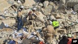 Nhân viên cứu hộ tìm kiếm người sống sót tại hiện trường sau một vụ không kích ở Idlib, Syria.